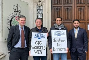 """Four people holding signs with the slogans """"gig workers win"""" and """"justice for drivers"""""""