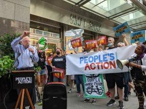 "Sen. Bernie Sanders speaks in front of a crowd of ten people carrying signs that read ""People over profits"""