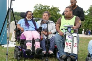 """Three people in wheelchairs speak in front of a microphone holding a sign that """"Fully fund home-based"""