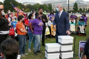 Sen. Bob Casey stands in front of a group of 30 people with a box of stories from careworkers.