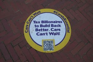 """A circular placard on the sidewalk reads """"Tax Billionaires to Build Back Better, Care Can't Wait!"""" in blue text."""
